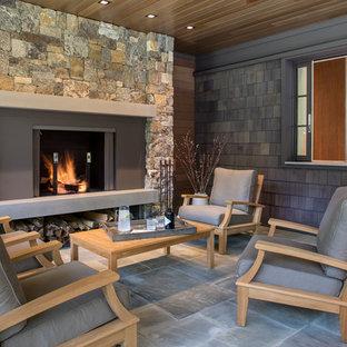 Esempio di un grande patio o portico stile rurale dietro casa con pavimentazioni in pietra naturale e un tetto a sbalzo