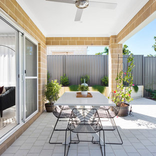 Photo of a contemporary backyard patio in Perth with a container garden, concrete pavers and a roof extension.