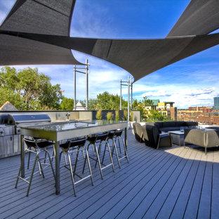 Immagine di un grande patio o portico design dietro casa con pedane e un parasole
