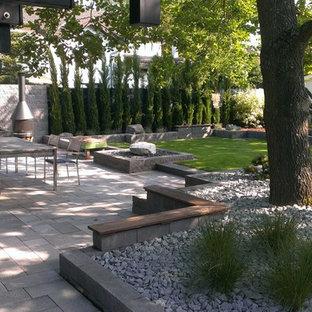 Idee per un grande patio o portico design con un tetto a sbalzo e un caminetto