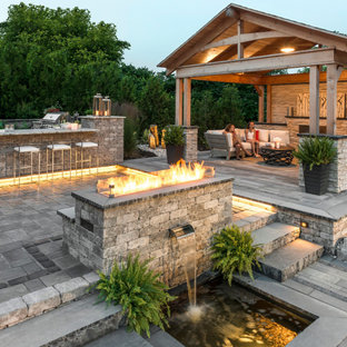 Patio kitchen - large transitional backyard concrete paver patio kitchen idea in New York with a pergola