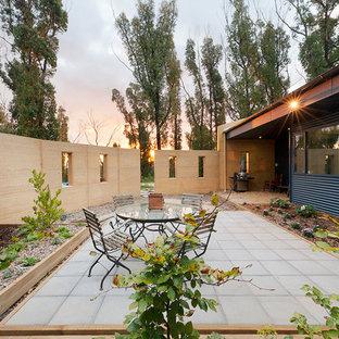Diseño de patio actual, de tamaño medio, sin cubierta, en patio trasero, con adoquines de hormigón y huerto