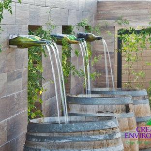 Idee per un patio o portico stile americano di medie dimensioni e dietro casa con fontane, ghiaia e nessuna copertura