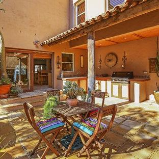 Cette image montre une terrasse avec une cuisine extérieure sud-ouest américain avec des pavés en béton et une extension de toiture.