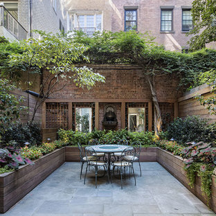 Inspiration for a large classic back patio in New York with a potted garden, no cover and natural stone paving.