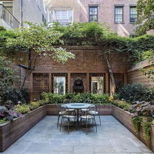 Inspiration pour une grande terrasse avec des plantes en pots arrière traditionnelle avec aucune couverture et des pavés en pierre naturelle.