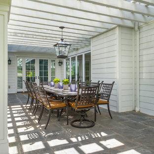 Esempio di un patio o portico chic di medie dimensioni e dietro casa con un giardino in vaso, pavimentazioni in mattoni e un tetto a sbalzo
