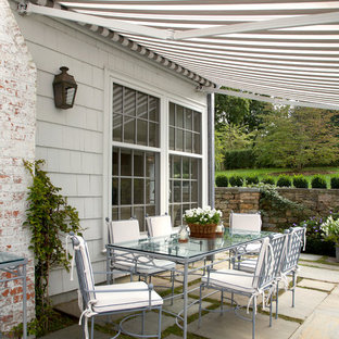 Inspiration for a medium sized classic side patio in New York with natural stone paving and an awning.