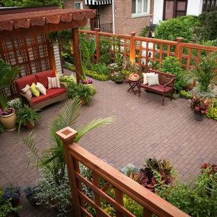 Patio - small traditional backyard brick patio idea in Chicago with a pergola
