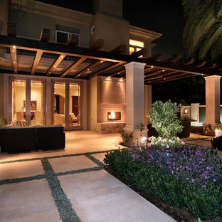 Inspiration for a mediterranean backyard stone patio remodel in Orange County with a fire pit and a pergola
