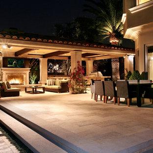 Esempio di un patio o portico mediterraneo di medie dimensioni e dietro casa con un gazebo o capanno e un focolare