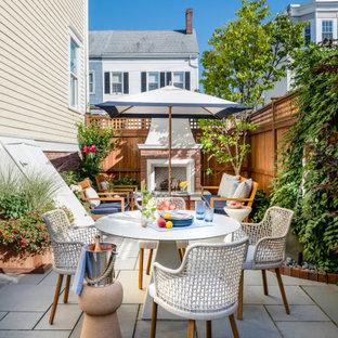 Esempio di un patio o portico classico di medie dimensioni e nel cortile laterale con un caminetto, pavimentazioni in pietra naturale e nessuna copertura