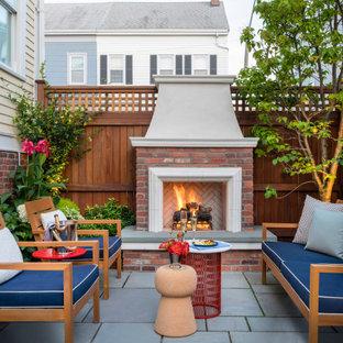 Ispirazione per un patio o portico tradizionale di medie dimensioni e nel cortile laterale con un caminetto, pavimentazioni in pietra naturale e nessuna copertura