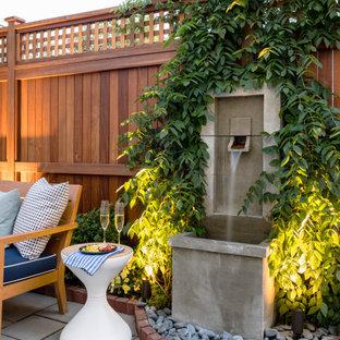 Ispirazione per un patio o portico tradizionale di medie dimensioni e nel cortile laterale con pavimentazioni in pietra naturale, nessuna copertura e fontane
