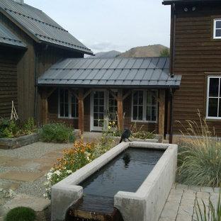 Idee per un ampio patio o portico country in cortile con fontane, pavimentazioni in pietra naturale e un tetto a sbalzo