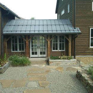 Idee per un ampio patio o portico country in cortile con ghiaia e un tetto a sbalzo