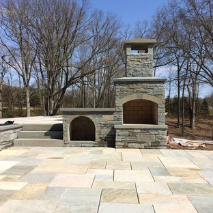 Inspiration for a large timeless backyard stone patio remodel in New York with a fire pit