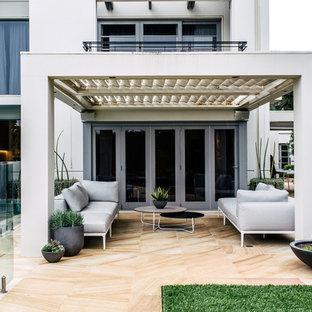 Создайте стильный интерьер: большой дворик на заднем дворе в современном стиле с растениями в контейнерах и дорожками из брусчатки из камня - последний тренд