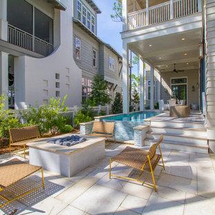 Cette photo montre une terrasse arrière bord de mer avec un foyer extérieur, une terrasse en bois et une extension de toiture.