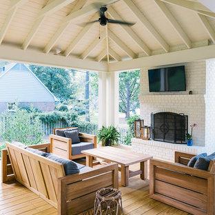 Idee per un grande patio o portico chic dietro casa con un tetto a sbalzo