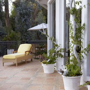 Esempio di un patio o portico eclettico con piastrelle e nessuna copertura