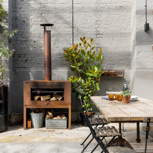 This is an example of an industrial courtyard patio in London with a container garden, concrete slab and no cover.