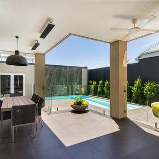 Esempio di un patio o portico vittoriano di medie dimensioni e dietro casa con piastrelle e un tetto a sbalzo