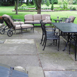 This is an example of a large victorian backyard patio in Other with a container garden, natural stone pavers and no cover.