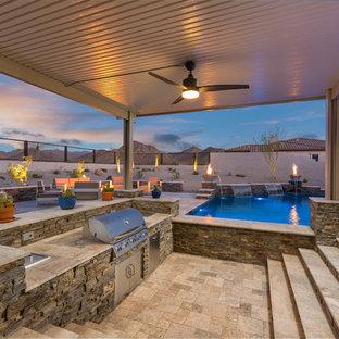 Ispirazione per un grande patio o portico design dietro casa con un caminetto e piastrelle