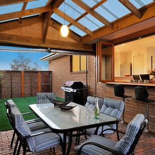 Ispirazione per un piccolo patio o portico minimalista nel cortile laterale con pavimentazioni in mattoni e una pergola