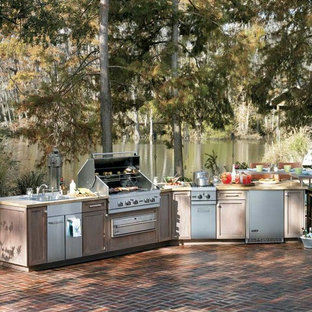Example of a large classic backyard brick patio kitchen design in Other with no cover