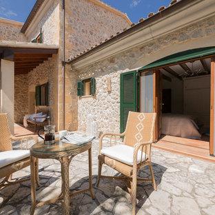Ejemplo de patio mediterráneo, sin cubierta, en patio trasero, con adoquines de piedra natural