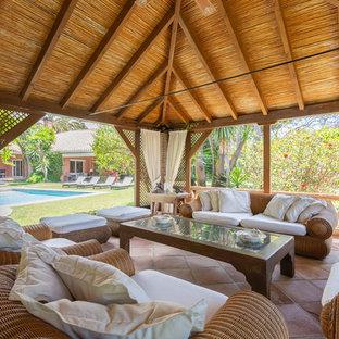 Foto de patio exótico, grande, con suelo de baldosas y cenador