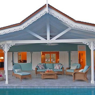 Immagine di un patio o portico tropicale in cortile con fontane, piastrelle e un tetto a sbalzo