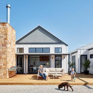 Foto di un patio o portico country di medie dimensioni e in cortile con un caminetto, pedane e un tetto a sbalzo