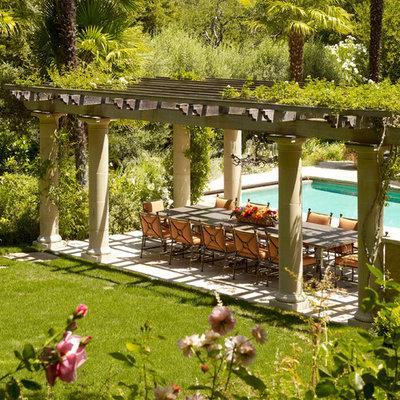 Patio - huge mediterranean backyard stone patio idea in San Francisco with a pergola