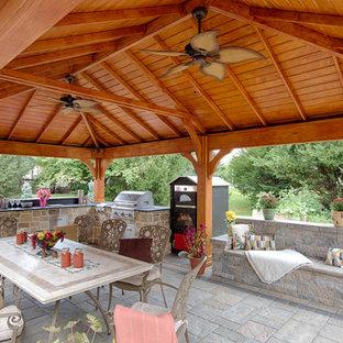 Immagine di un grande patio o portico tradizionale dietro casa con pavimentazioni in cemento e un gazebo o capanno