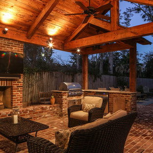 Inspiration for a large timeless backyard brick patio kitchen remodel in New Orleans with a roof extension