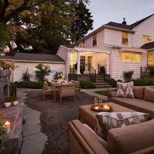 Immagine di un patio o portico chic dietro casa e di medie dimensioni con un focolare e ghiaia