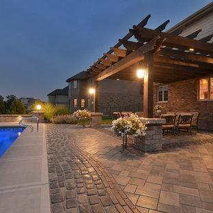 Ispirazione per un grande patio o portico eclettico dietro casa con un focolare, pavimentazioni in cemento e una pergola