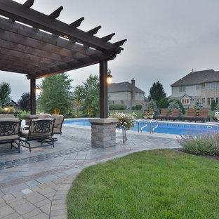 Immagine di un grande patio o portico eclettico dietro casa con un focolare, pavimentazioni in cemento e una pergola