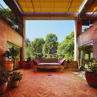 Large country patio in Other with brick paving, an awning and a potted garden.