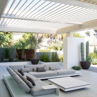 Imagen de patio actual, grande, en patio trasero, con suelo de baldosas y pérgola
