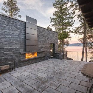 Diseño de patio rústico, sin cubierta, en patio lateral, con chimenea y adoquines de hormigón