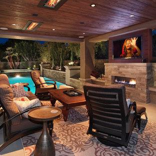 Aménagement d'une grande terrasse arrière contemporaine avec un foyer extérieur, des pavés en béton et une extension de toiture.