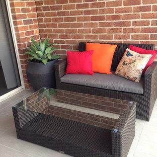 Immagine di un piccolo patio o portico minimalista dietro casa con lastre di cemento e un parasole