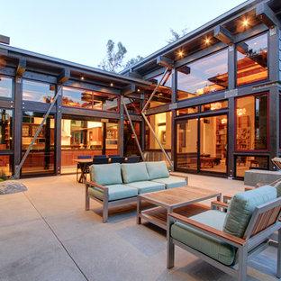 Immagine di un grande patio o portico industriale dietro casa con un focolare, lastre di cemento e nessuna copertura