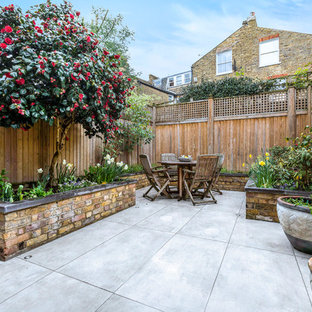 This is an example of a medium sized classic back patio in London with a potted garden, natural stone paving and no cover.