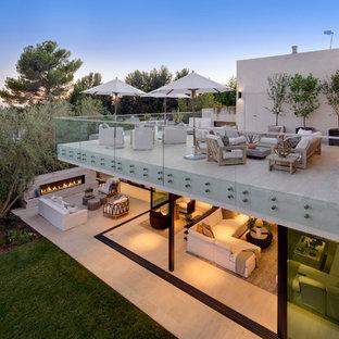 Foto di un ampio patio o portico minimal dietro casa con un focolare, piastrelle e un tetto a sbalzo