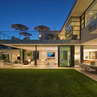Idee per un ampio patio o portico minimal dietro casa con un focolare, piastrelle e un tetto a sbalzo